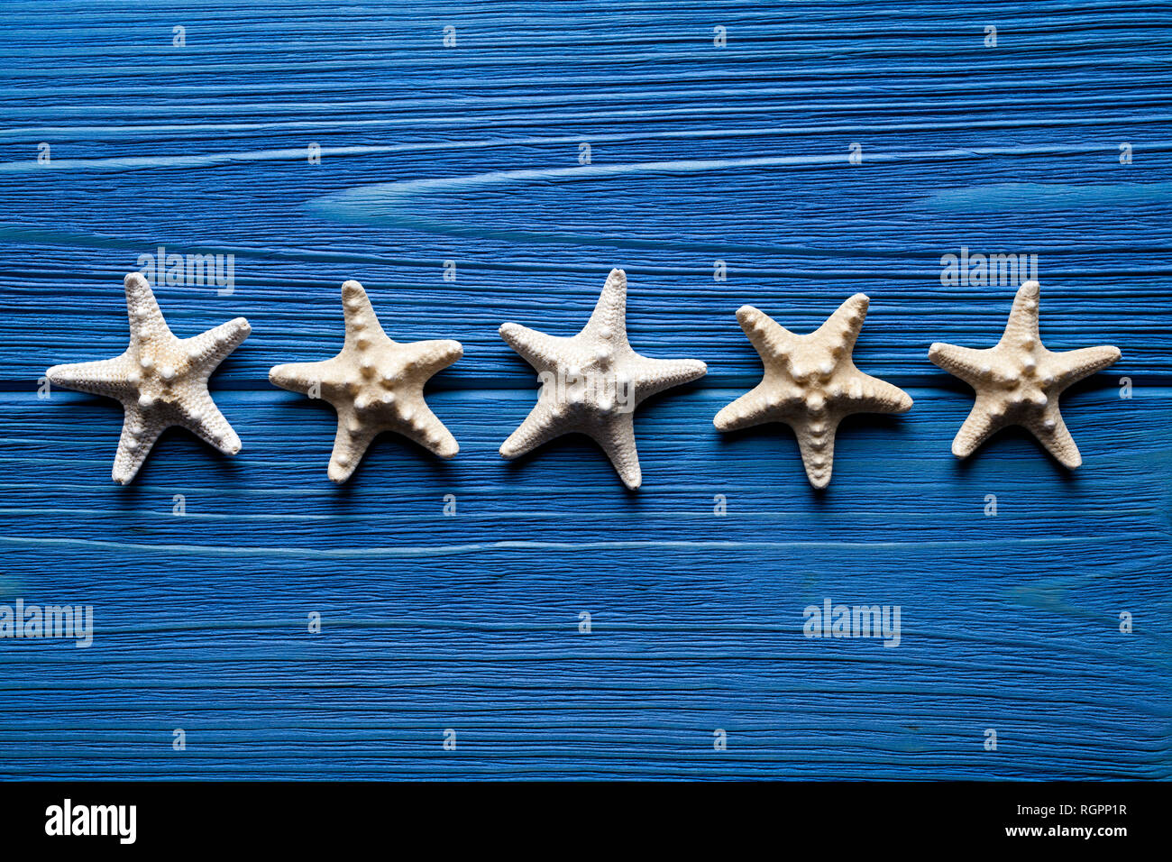 Starfishes on blue planks background - Stock Image