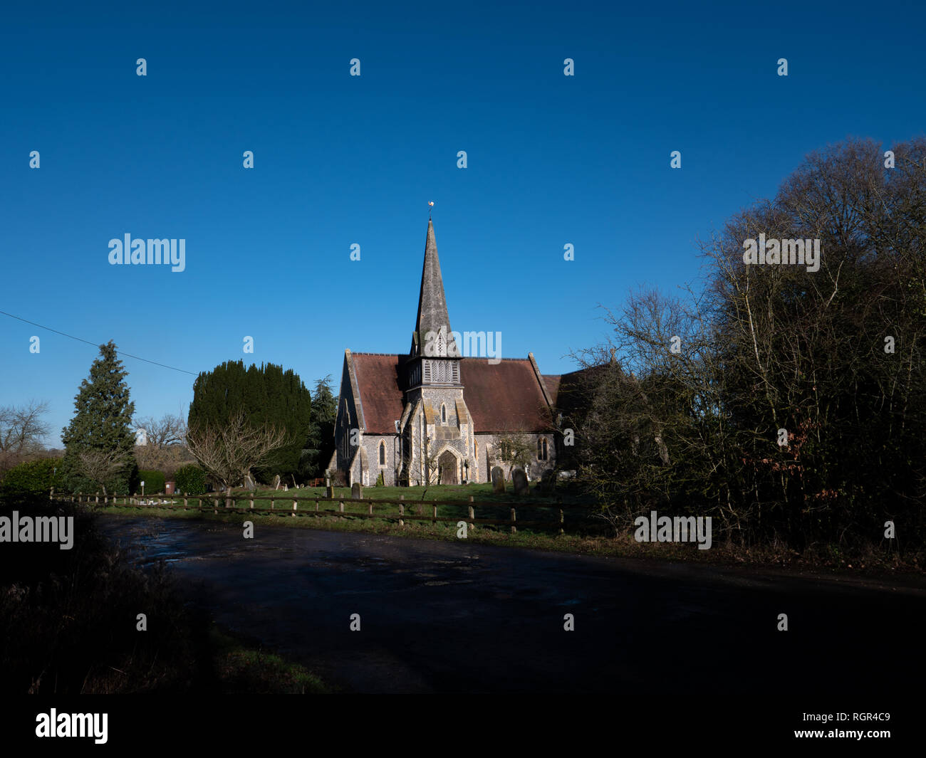 English country church with spire against blue sky. St James Barkham Stock Photo