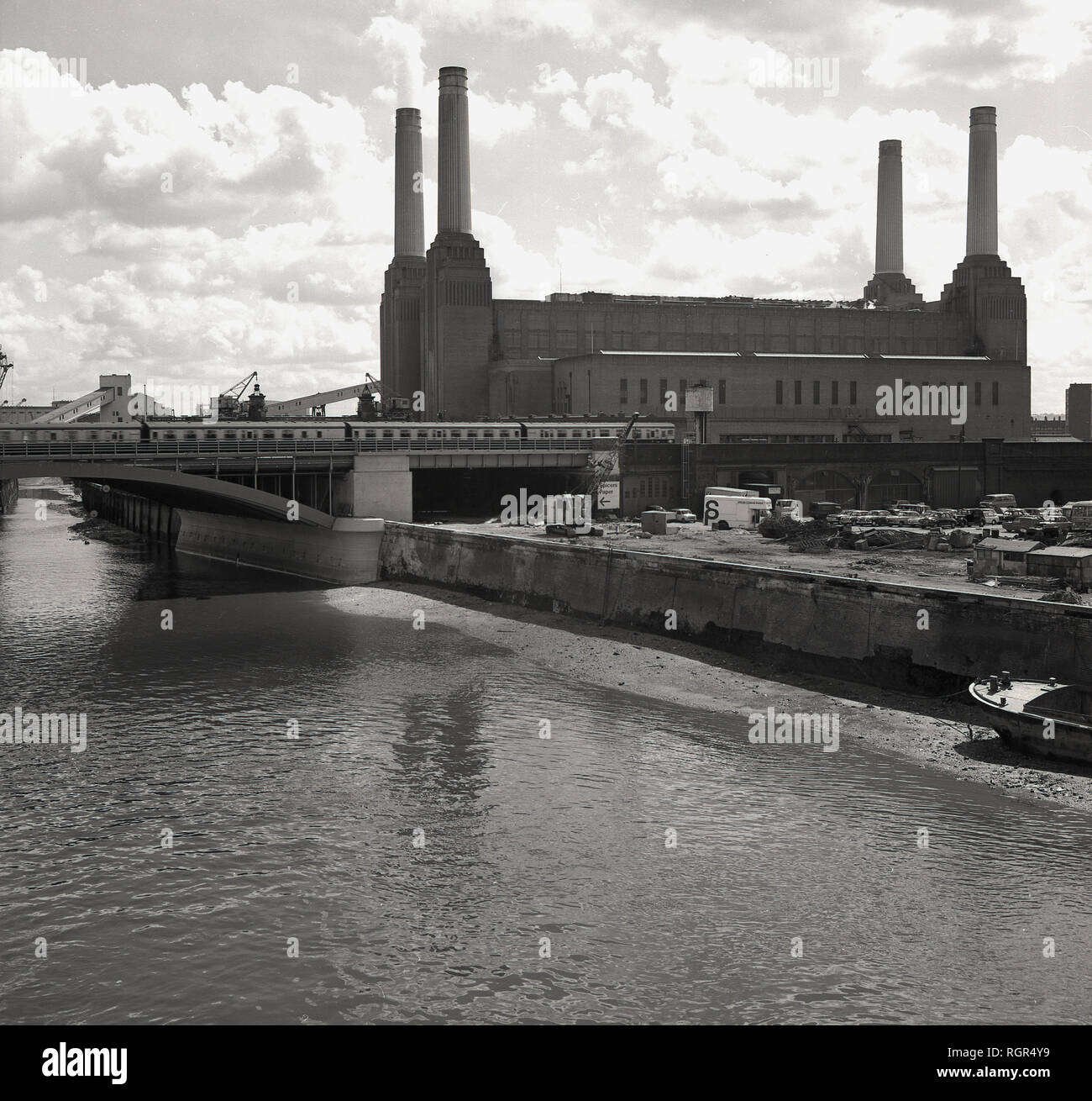 1950s, historical, view of Battersea Power Station at Nine Elms, Battersea on the South bank of the River Thames, London, England, The coal-fired power station was in fact two power stations in a single building, Battersea A was constructed in the 1930s and Battersea B between 1953-1955, with both being built to a nearly identical design, providing the iconic four-chimney structure seen in the picture. Created by the famous architect, Sir Giles Gilbert Scott, construction started in 1929 and it became one of the largest brick buildings in the world. It was finally decommissioned in 1983. - Stock Image