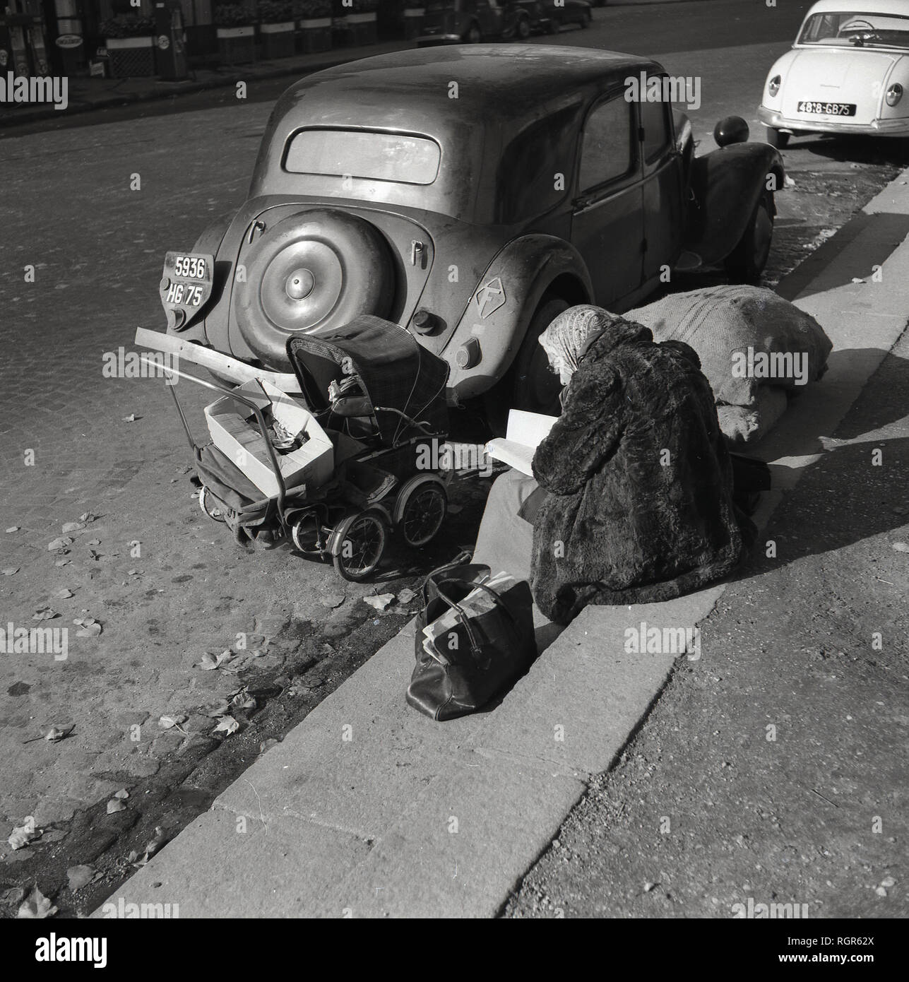 1950s, Paris, France, elderly lady, possibly a bag lady or vagabond, wearing a fur coat sitting beside a road and by parked cars with a small pram and her possessions with whilst reading a book. - Stock Image
