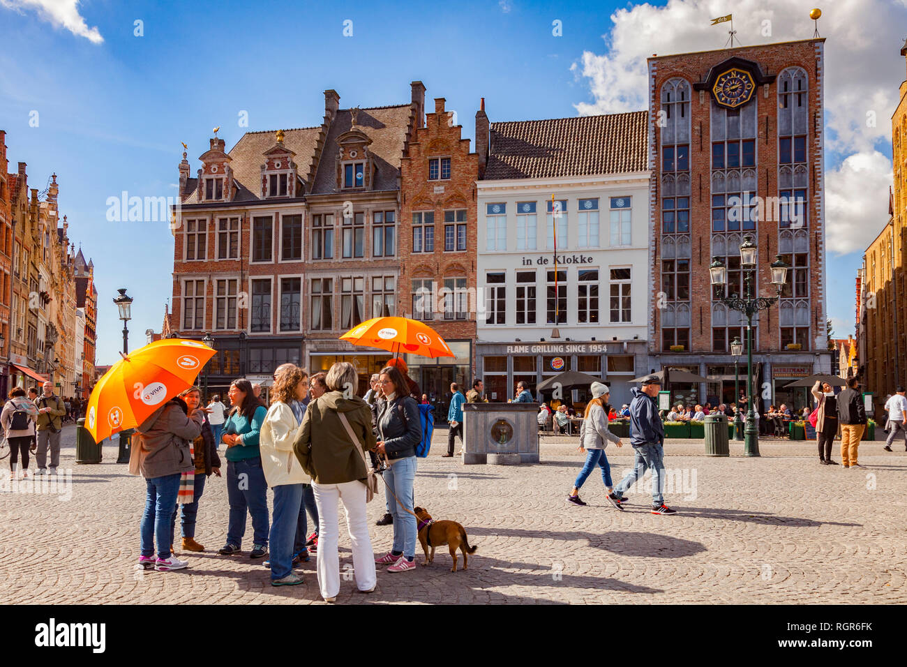 25 September 2018: Bruges, Belgium - Tour group under orange umbrellas in the centre of the city, Markt Square, on a sunny, autumn day with glorious b Stock Photo