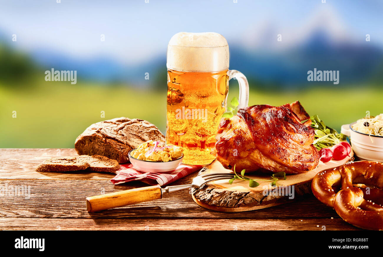 Traditional German cuisine, Schweinshaxe roasted ham hock, pretzel with obatzter cheese spread and glass of pale beer on wooden table - Stock Image