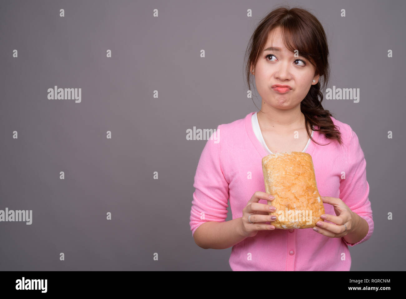 Young beautiful Asian woman holding piece of bread - Stock Image