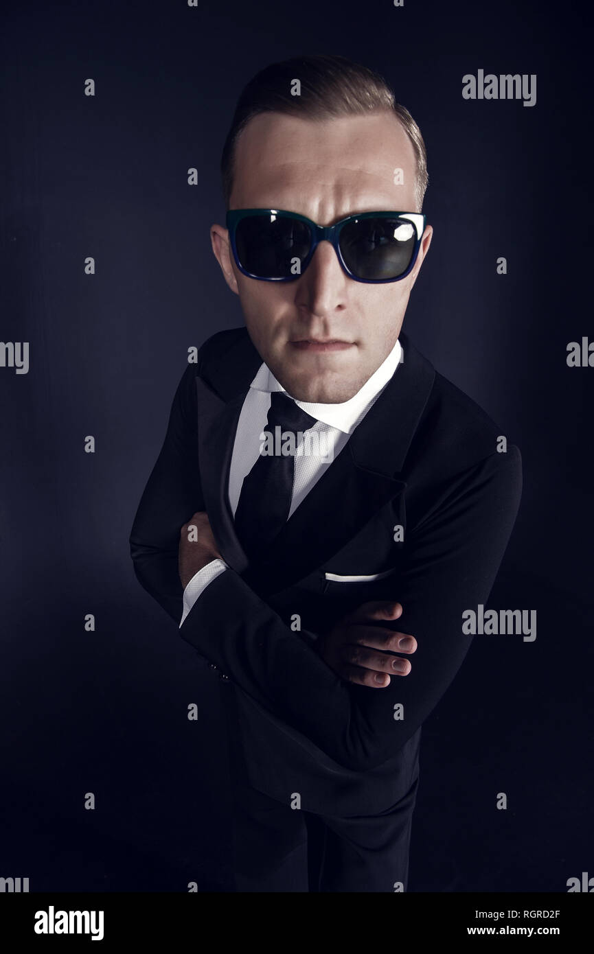 Businessman man in black suit and sunglasses on dark background. Secret, conspiracy or spy concept. Fashion, accessory, style, trend. - Stock Image