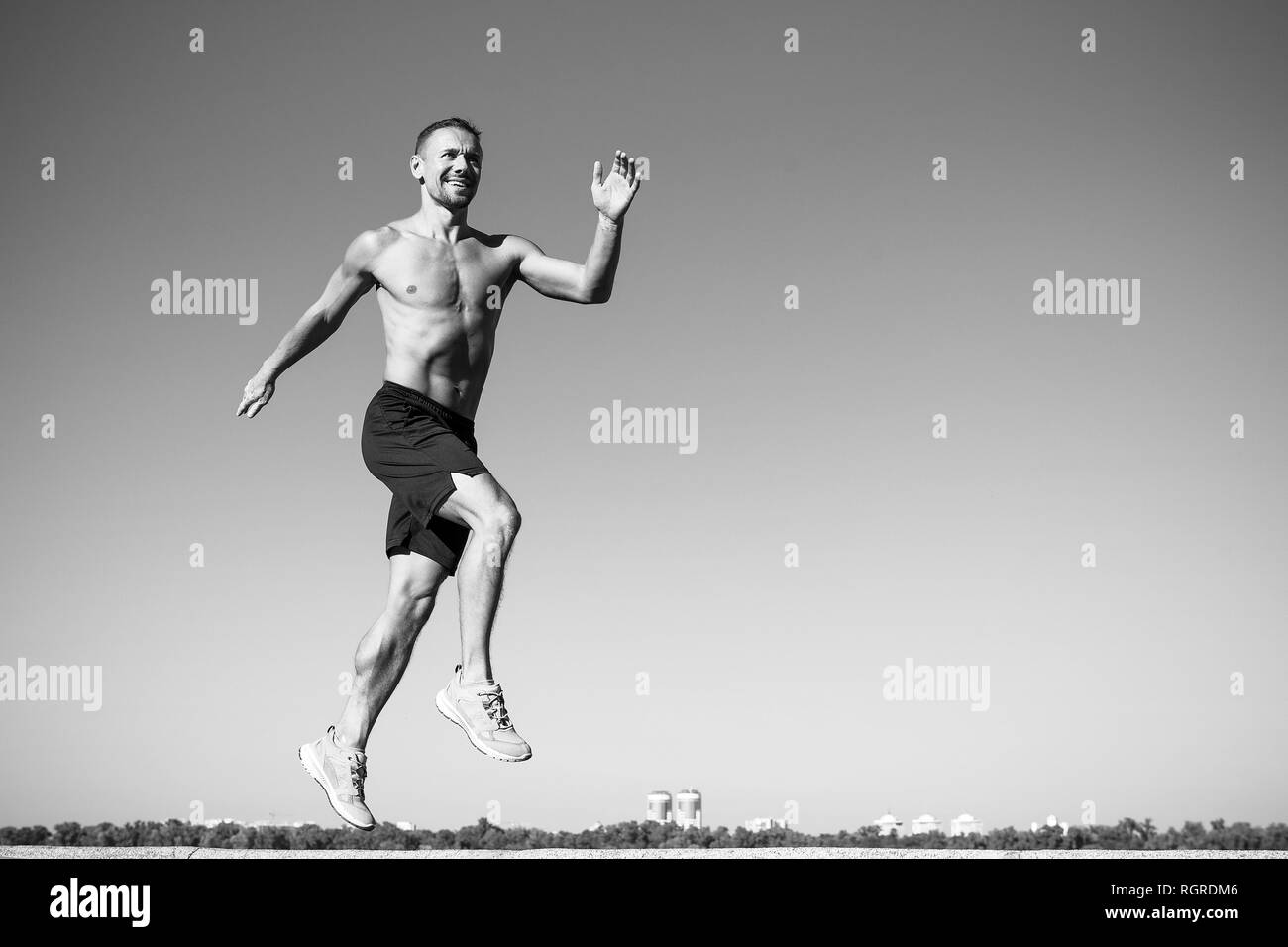 My favorite way to unwind is by going running. Success in sport. Muscular man jump in air. Man with muscular energy. Sport and fitness. The foundation of success in life is good health, copy space. - Stock Image