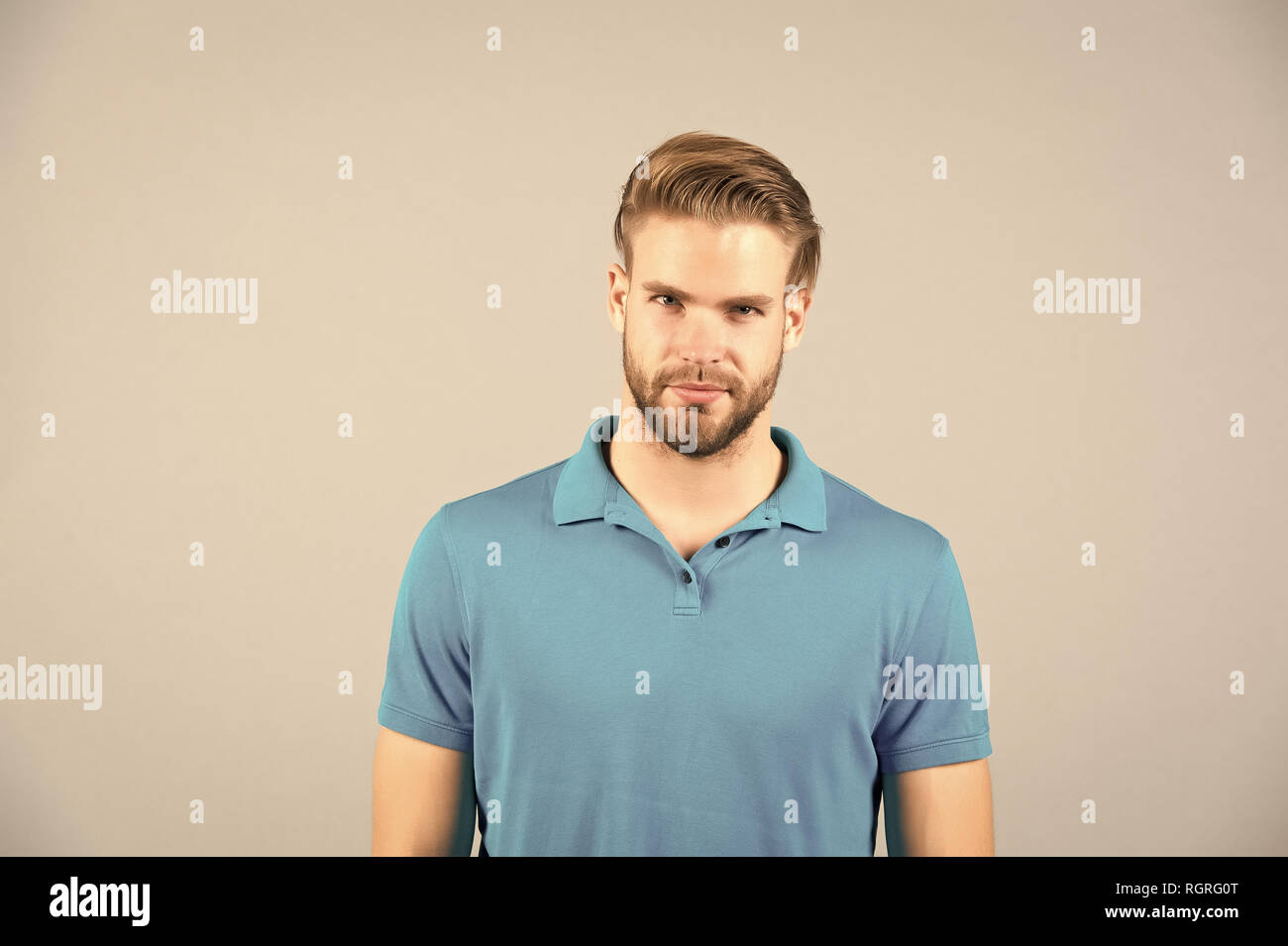 Mens beauty, fashion and style. Man in blue tshirt on grey background. Guy with bearded unshaven face. Macho with blond hair and stylish haircut. Hair care in salon or barbershop. - Stock Image