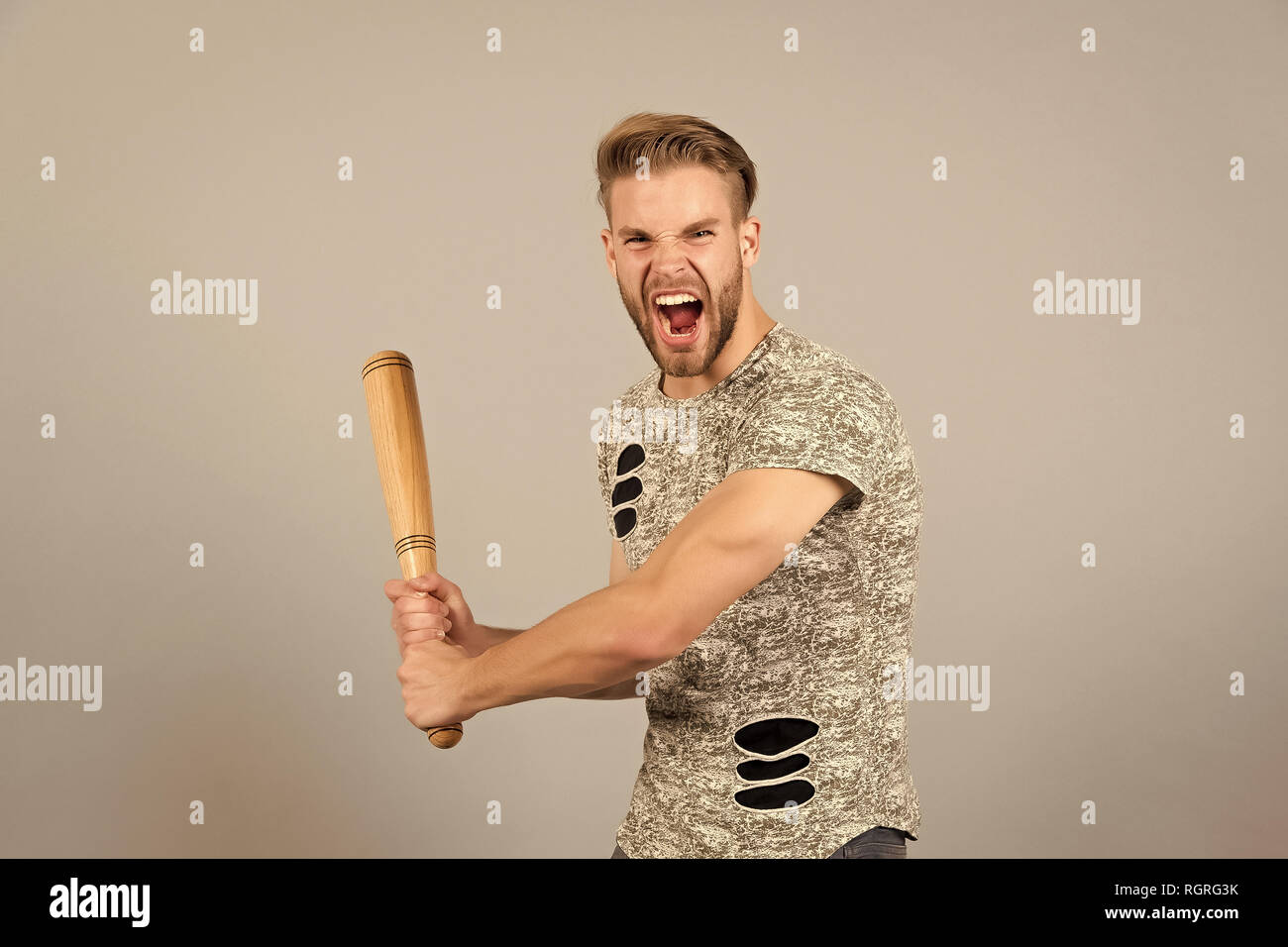 Bully man shouting aggressive face, grey background. Man with wooden bat ready to attack. Aggressive behaviour concept. Man bearded looks aggressive and threatening. Dangerous behaviour of hooligan. - Stock Image