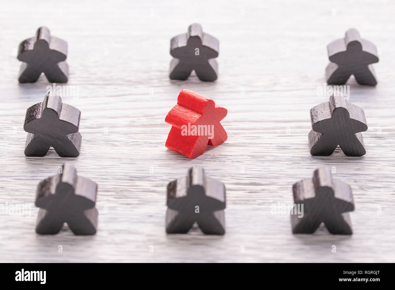 Uniqueness, individuality and difference. Red wooden figure in a crowd of different color on a white wooden table. The concept of disagreement with th - Stock Image