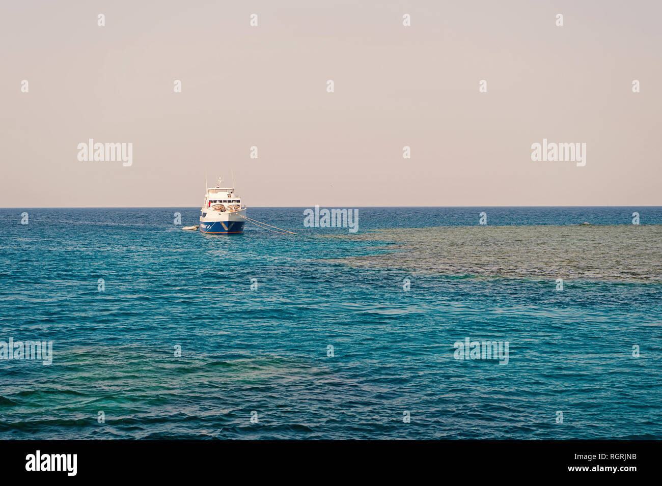 Ship anchored in blue sea on sunny sky horizon. Traveling by sea boat. Summer vacation and recreation. Water transport and vessel. - Stock Image