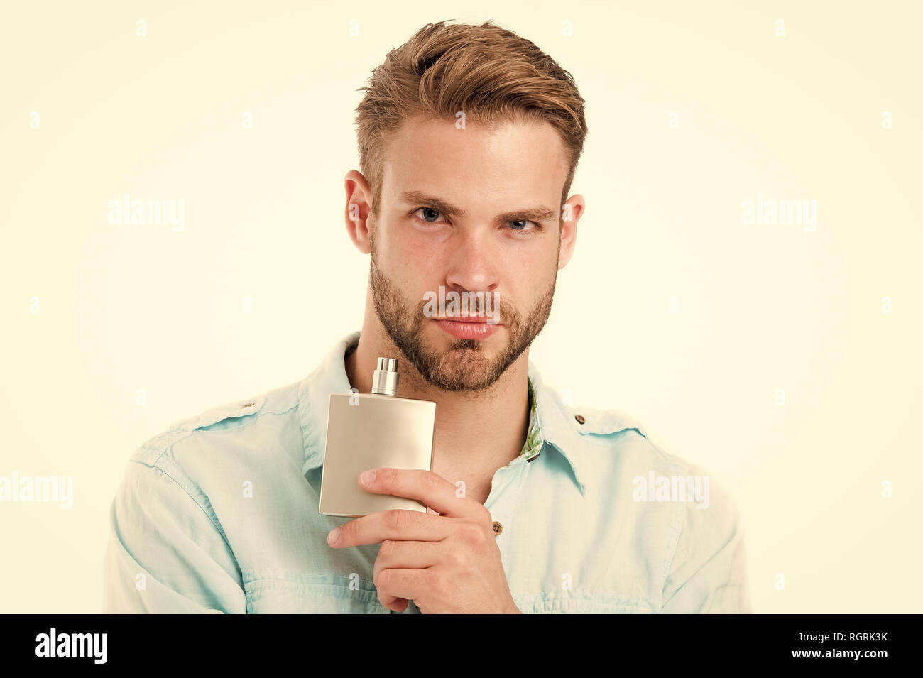 Guy hold perfume bottle. Bearded man with deodorant isolated on white background. Fashion cologne bottle. Hygiene and health. Getting fresh. - Stock Image