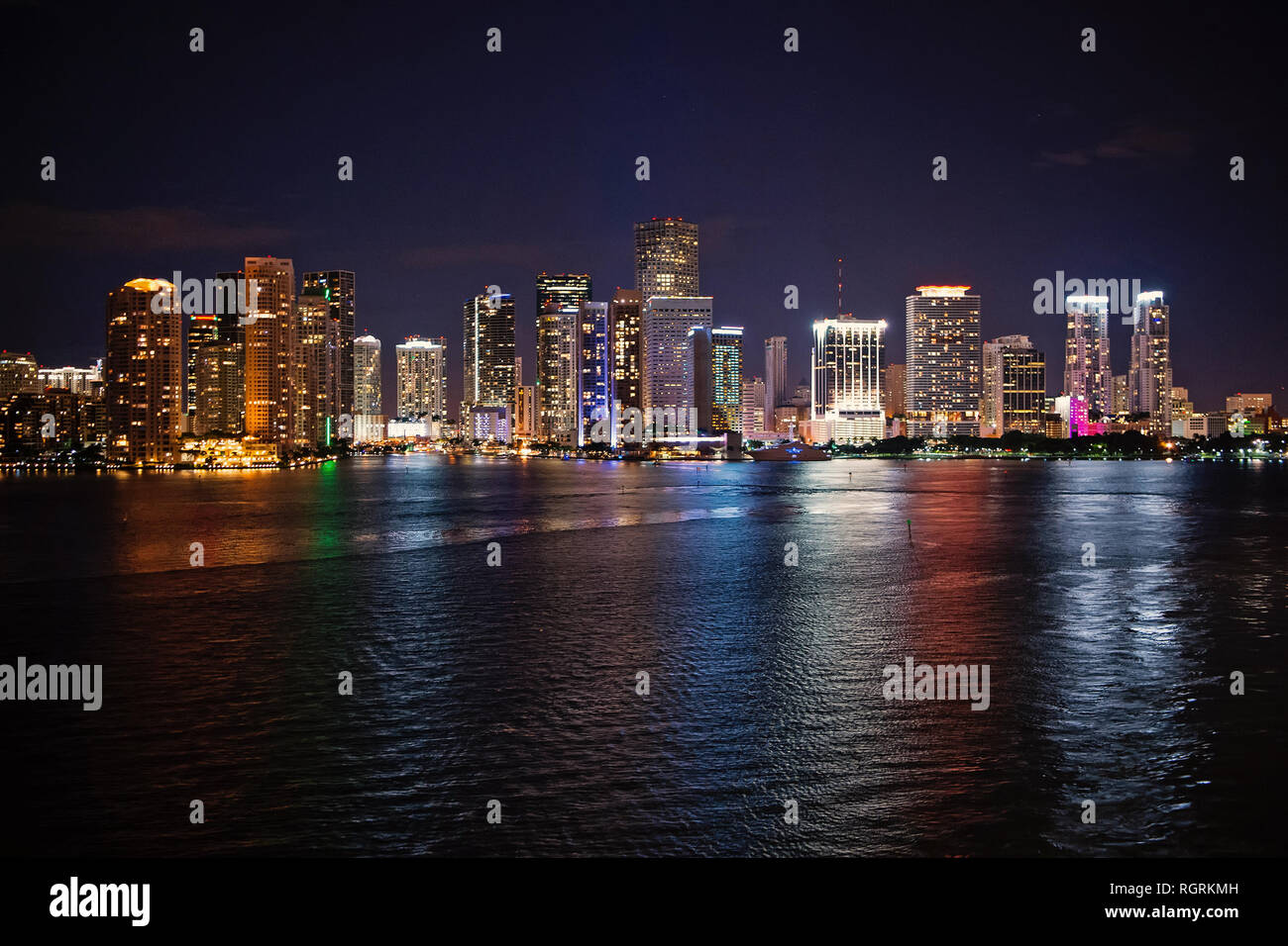 Miami city skyline panorama at night, usa. Skyscrapers illumination reflect on sea water in dusk. Architecture, structure, design. Building, construction, development. Wanderlust travel discovery - Stock Image
