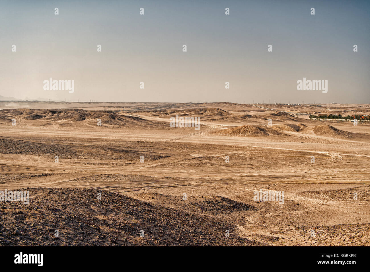 Desert landscape on clear blue sky background. Dune land with dry terrain surface. Ecology and global warming effect. Hopelessness and lifeless concept, copy space - Stock Image