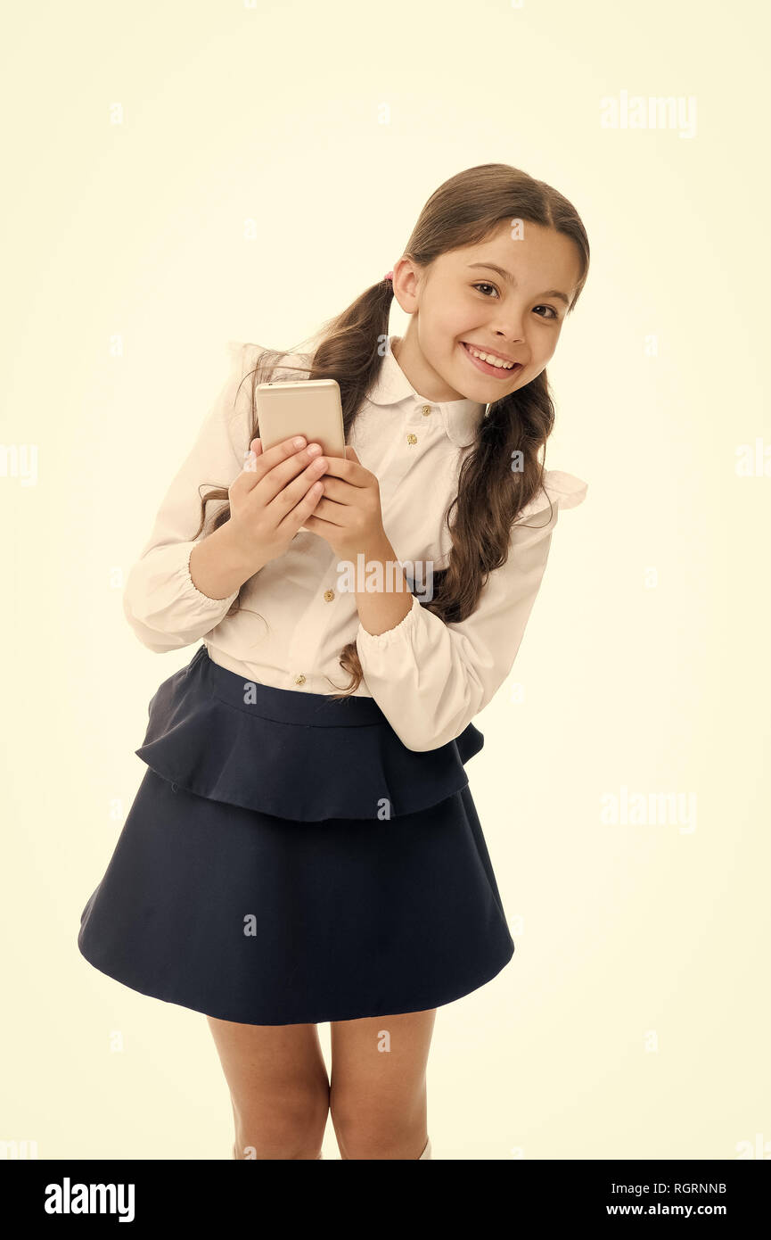 Girl cute long curly hair holds smartphone white background. Child girl school uniform clothes holds smartphone. Child school uniform smart kid happy face. Parental advisory concept. Always in touch. - Stock Image
