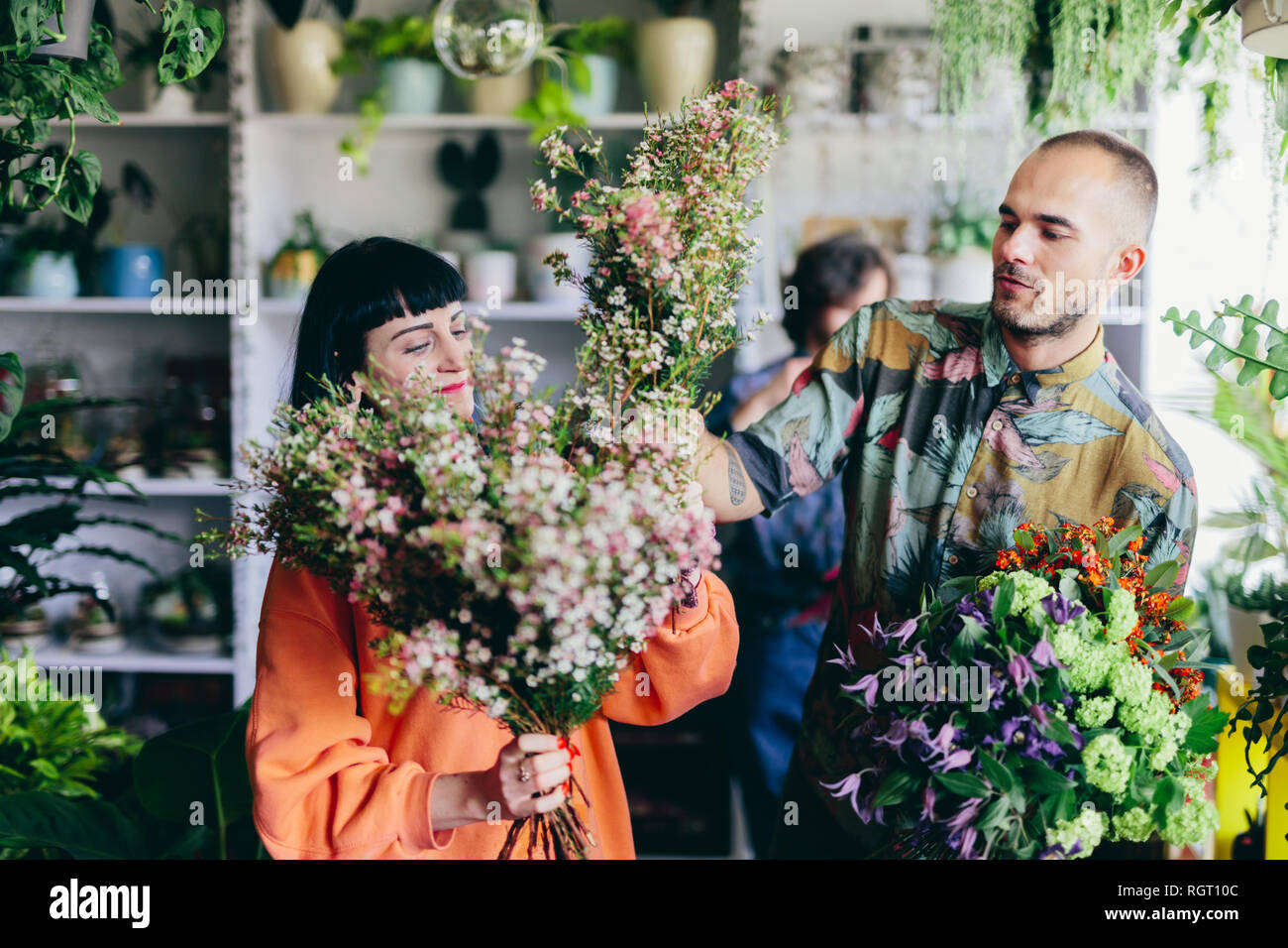 Man and woman working in the flower shop. Creative occupation, small business owners. Shopping and retailing. - Stock Image