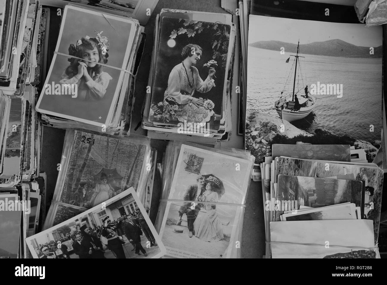 ATHENS, GREECE - SEPTEMBER 14, 2018: Collection of vintage postcards and old photographs at flea market antiques store. Black and white. - Stock Image