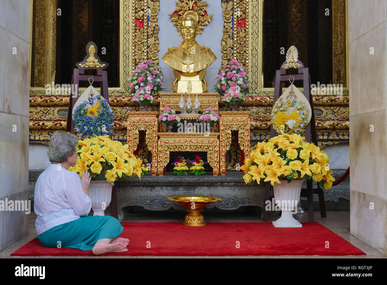 A woman praying in front of a bust of former Thai king Bhumipol Adulyadej, Wat Boworniwet, Bangkok, Thailand - Stock Image