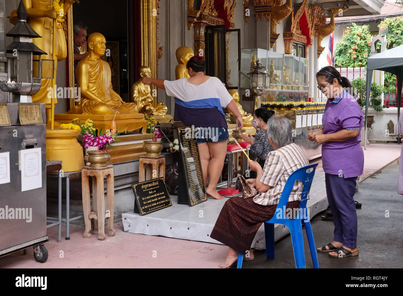 Worshippers at Wat Mai Amatarot, Bangkok, Samsen Road, Thailand, praying at a shrine with statues of the Buddha and revered monks - Stock Image