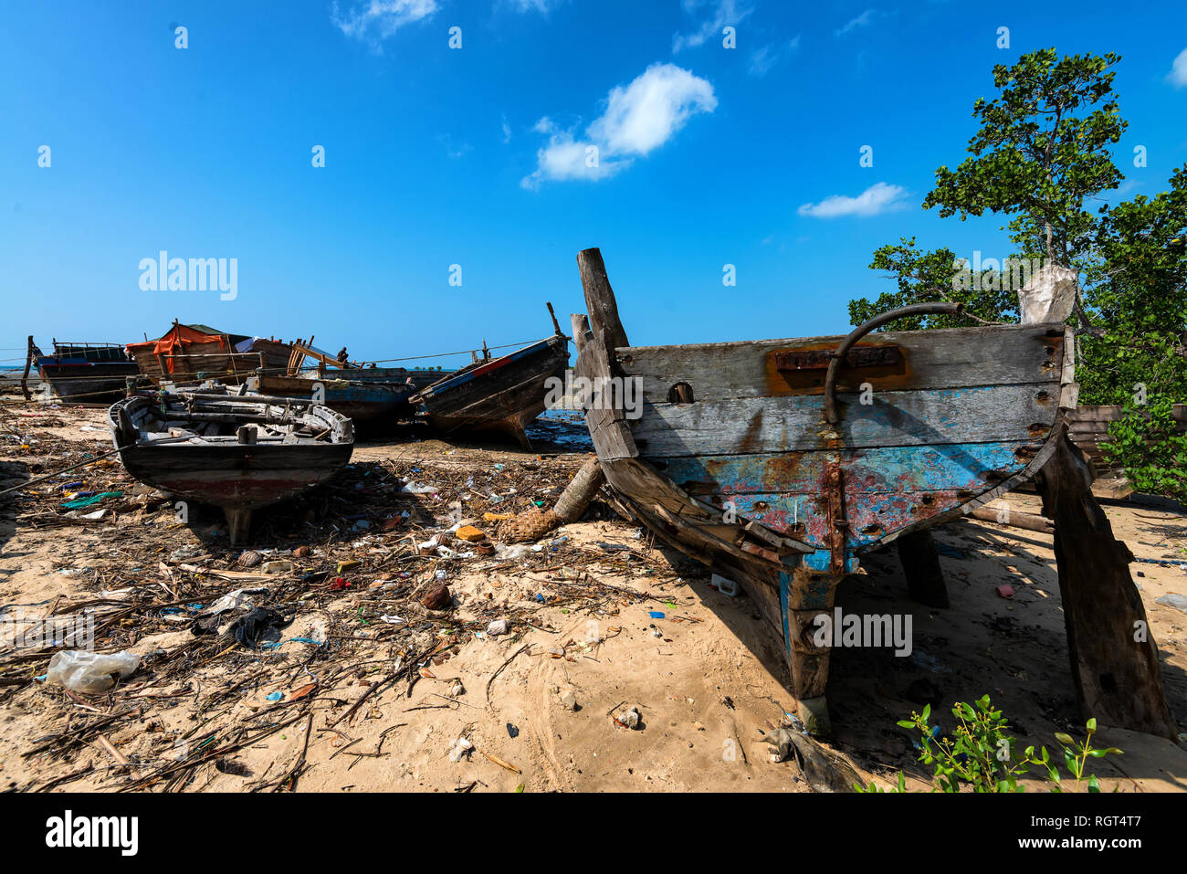 Zanzibar beach with old abandoned boats and trash - Stock Image