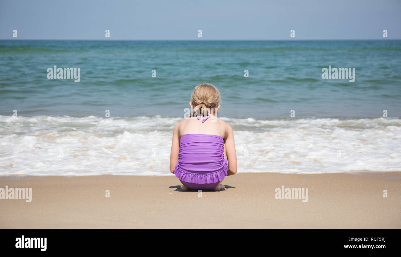 A 9 year old girl crouching in front of the waves coming ashore on the beach. - Stock Image