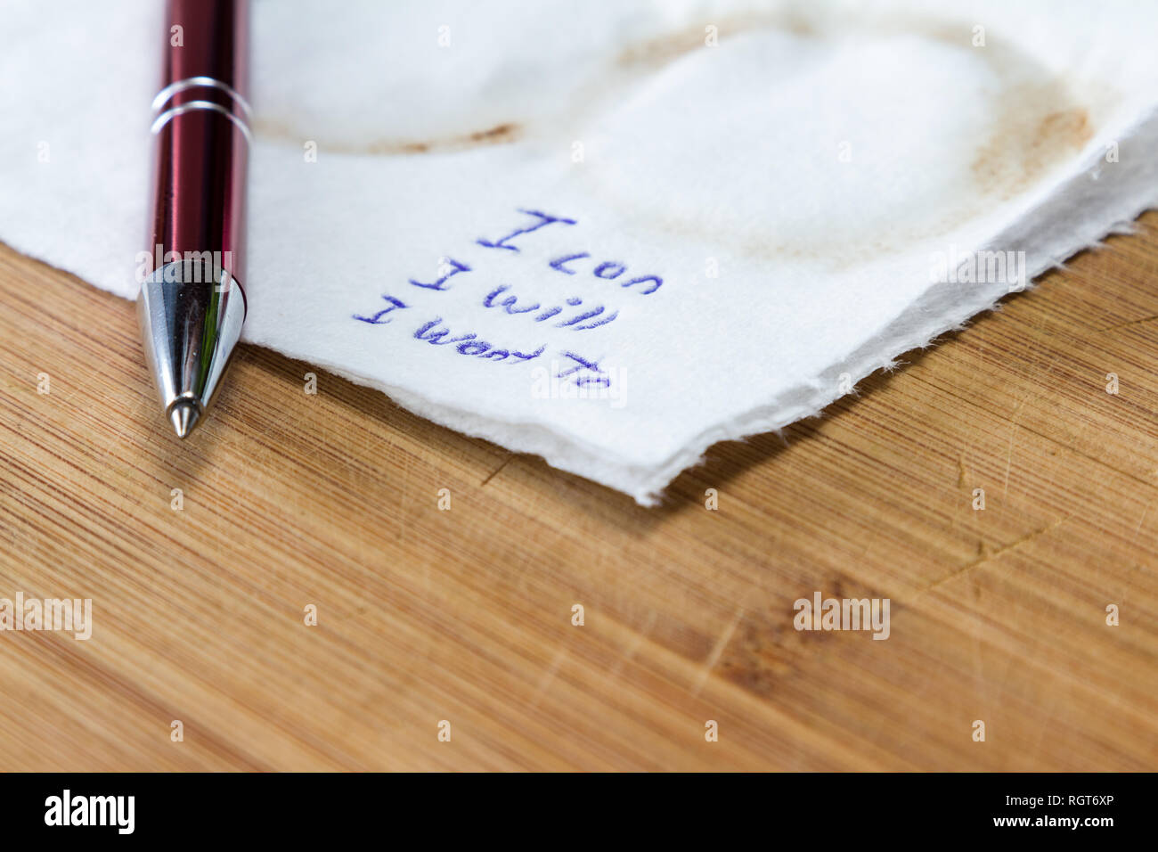 hand written note on a coffee stained napkin with an empowering message, I can I will I want to. Stock Photo
