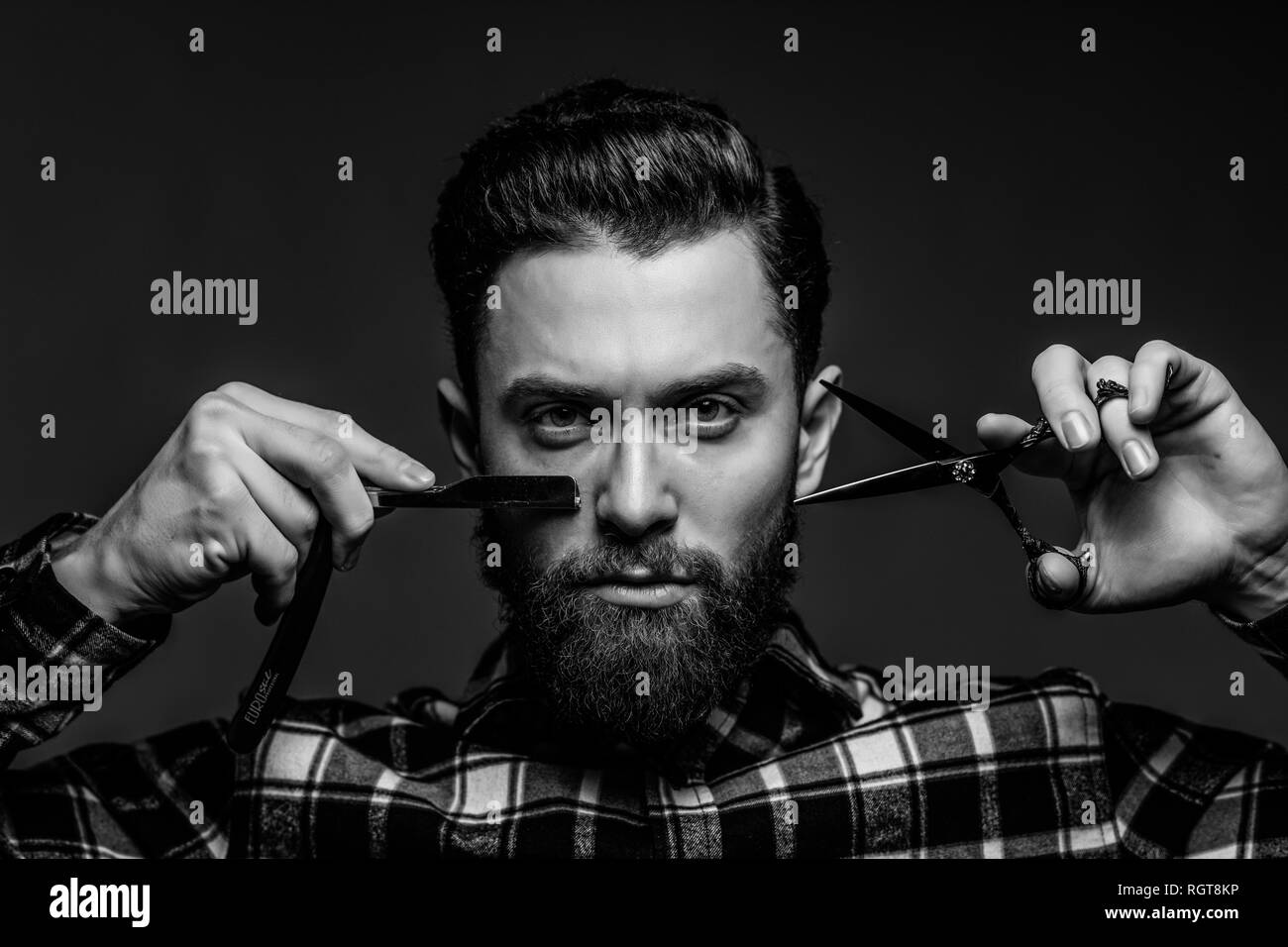 Man hairdresser in a plaid shirt holding a sharp professional scissors. Close-up - Stock Image