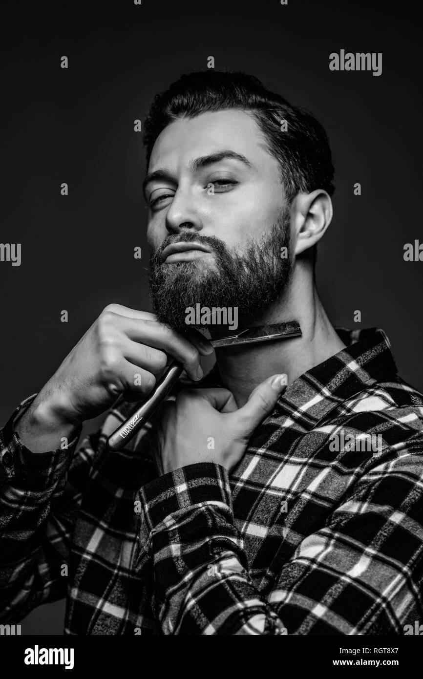 Handsome bearded hairdresser in stylish is holding a straight razor while standing on gray background Stock Photo