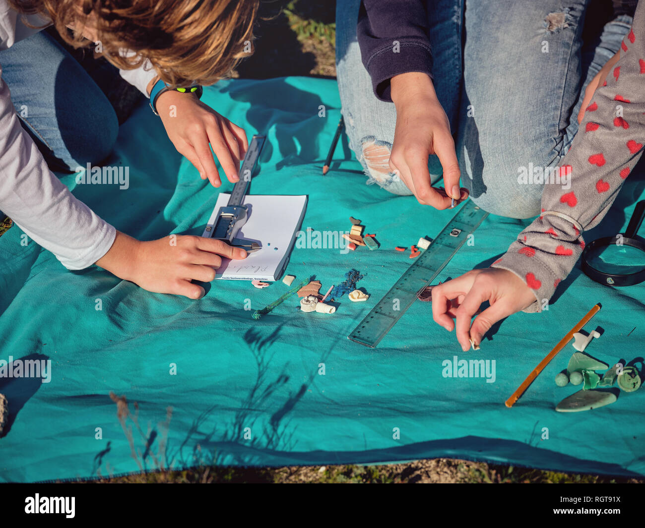 From above crop hands of persons gauging by vernier caliper little plastic things on paper on blue coverlet placed on ground - Stock Image