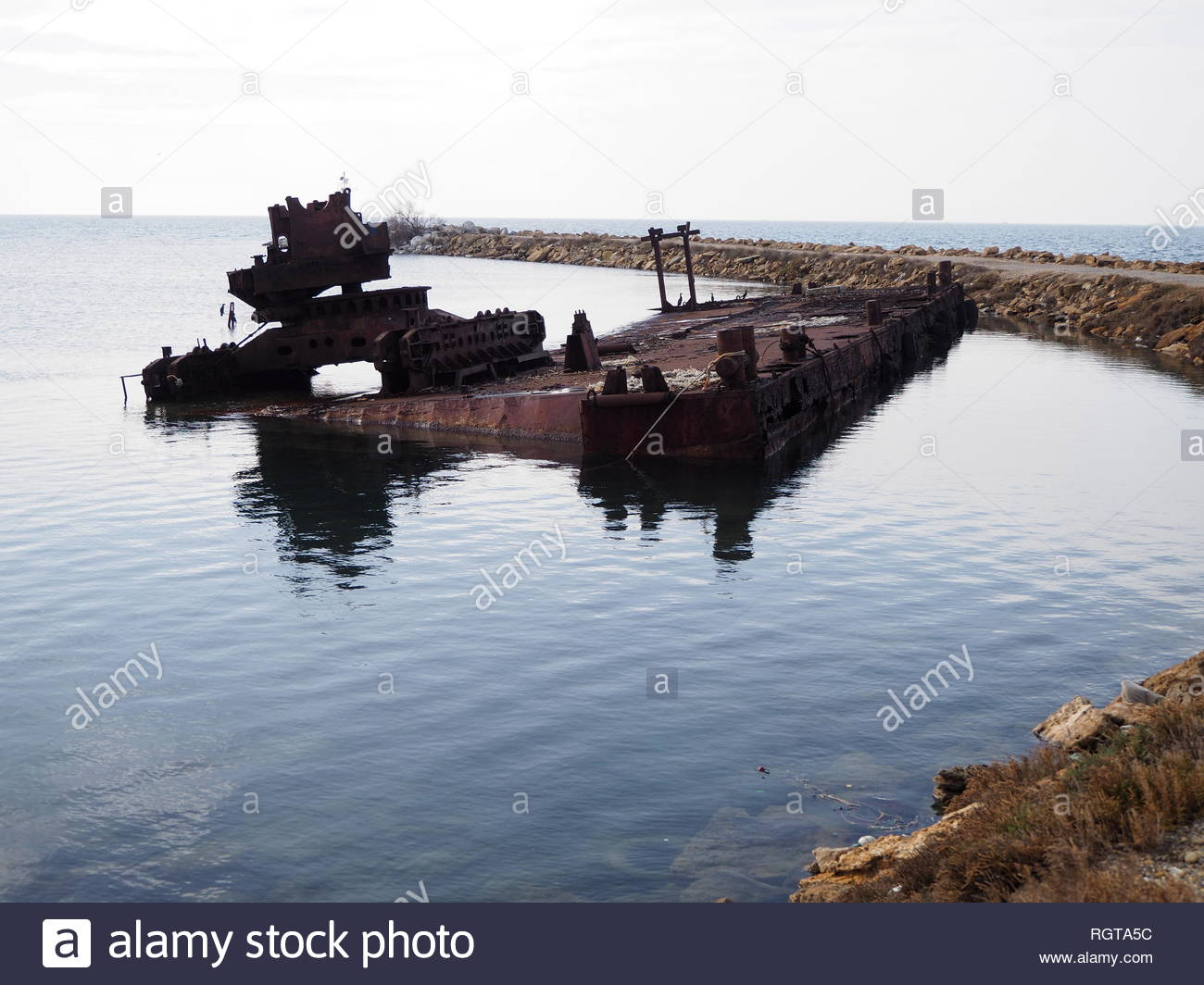 sunken  old and rusty floating crane at small fishing boats,port - Stock Image