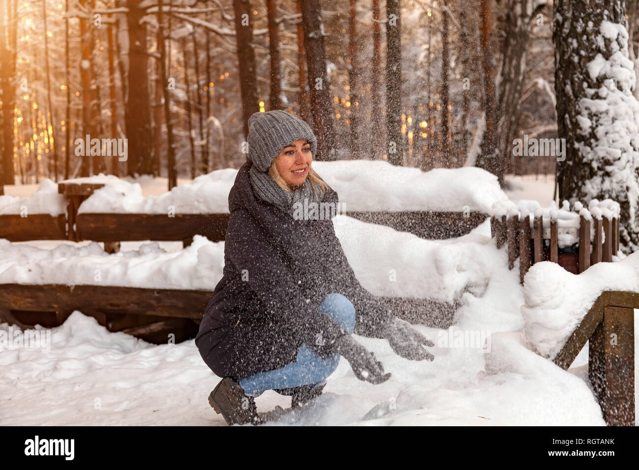 A young blonde squats in a winter forest in a gray hat and a dark blue jacket and watches the snow fall entranced and sparkles in the sun thrown by he - Stock Image