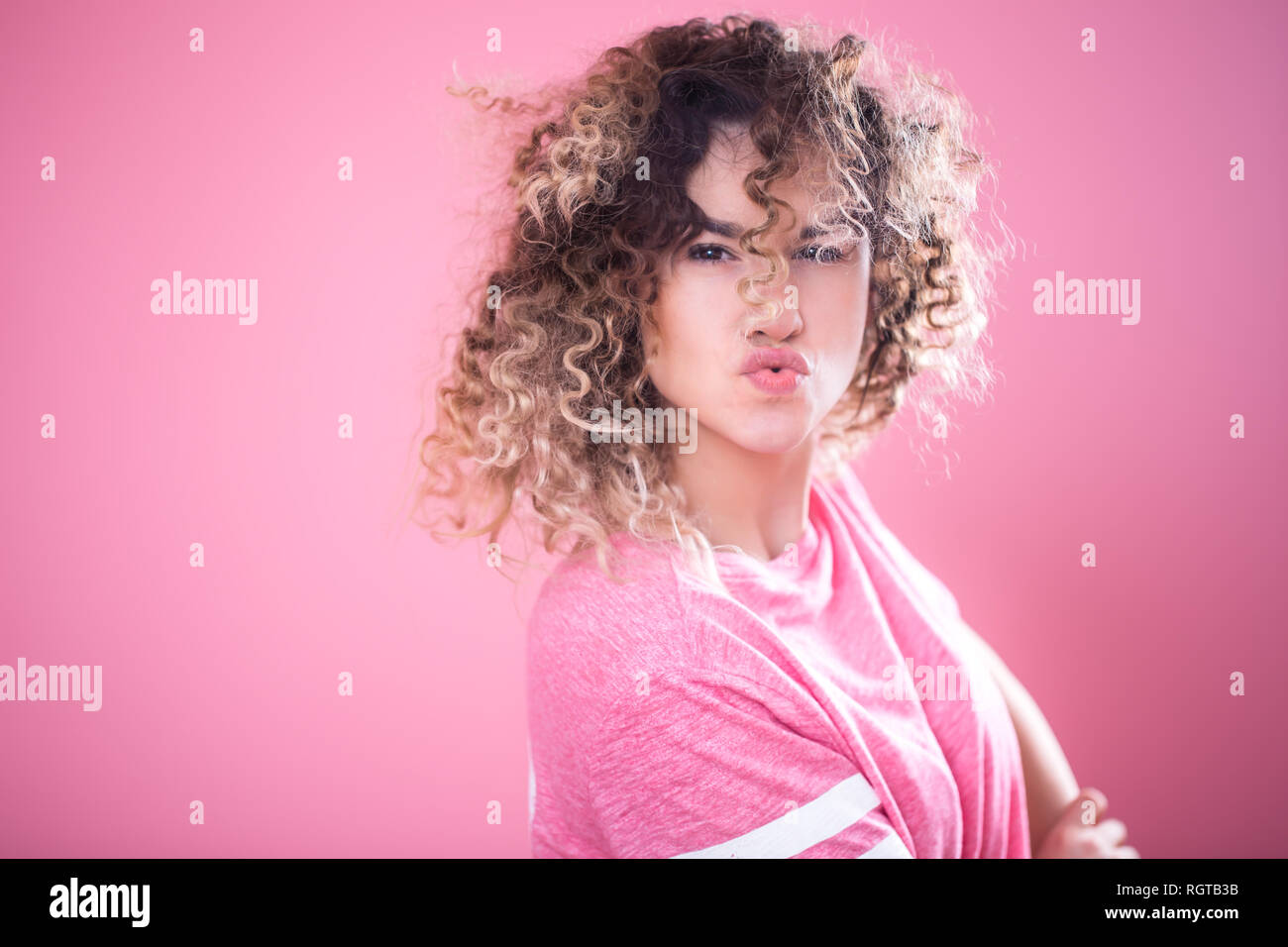 Portrait of a young emotional girl with pouted lips and curly hair in a loose pink t-shirt isolated on a pink background, place for text, emotion conc - Stock Image