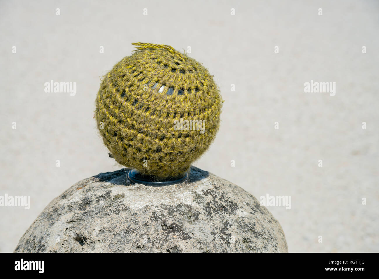 Interesting stone ball wrap in wool near Versailles at France - Stock Image