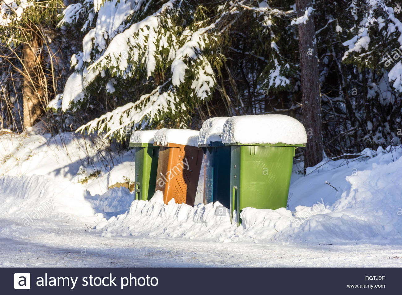Trash cans covered with snow standing along a path - Stock Image