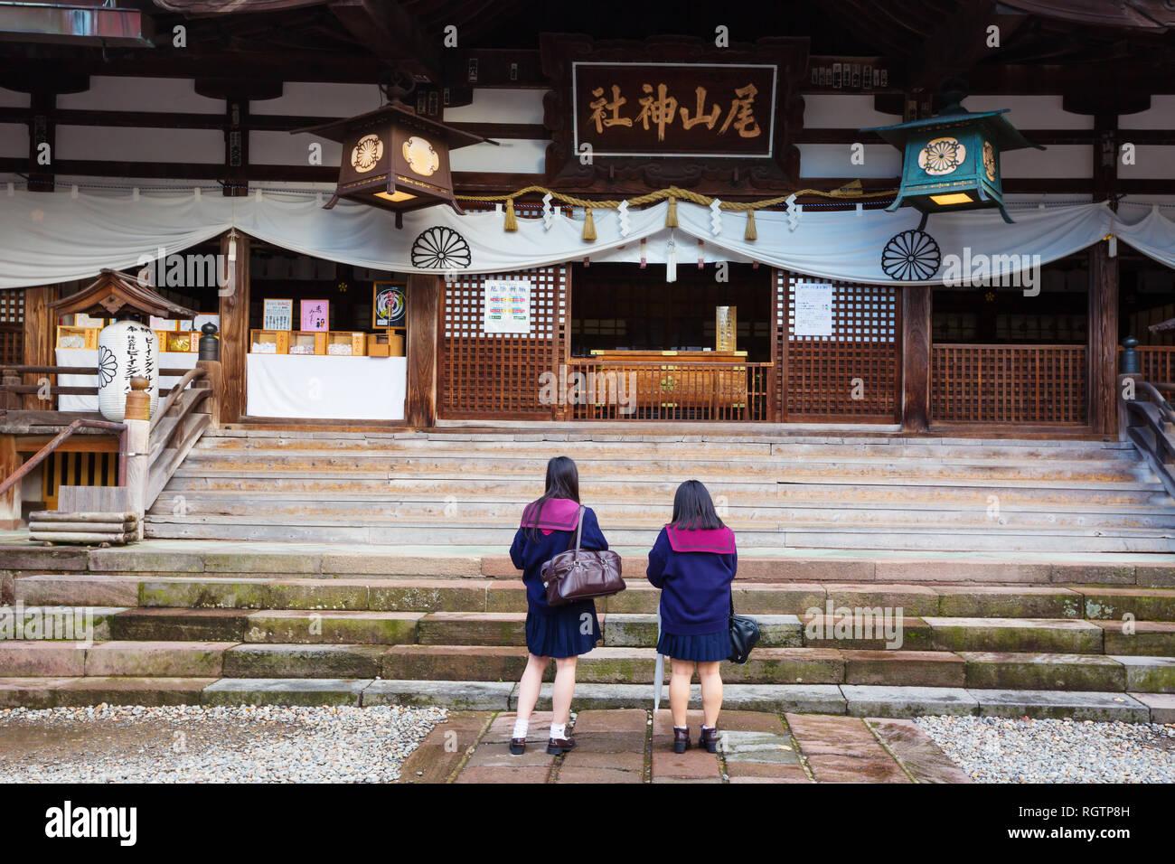 Two japanese schoolgirls pray at Oyama Jinja Shrine. Kanazawa, Japan - Stock Image