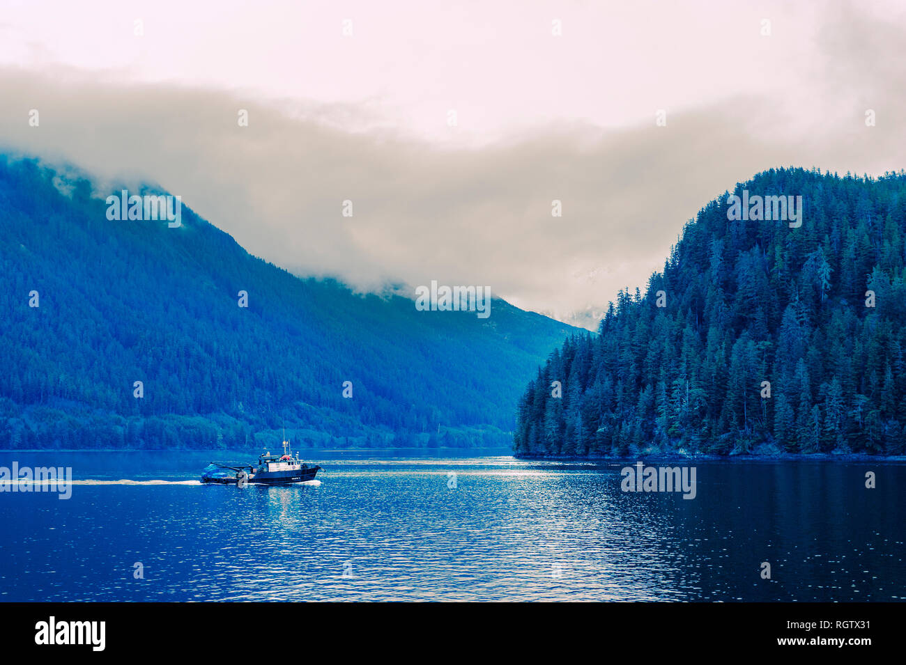 Commercial fishing tender departing Silver Bay fish processing plant near Sitka, Alaska, USA. Photography by Jeffrey Wickett, NorthLight Photography.  - Stock Image
