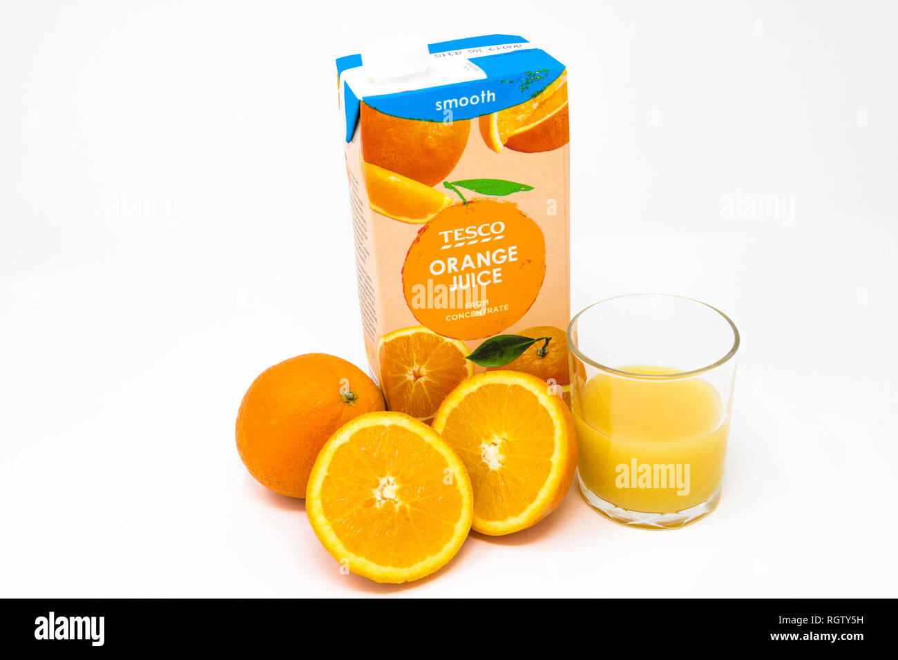 Carton of Tesco's orange juice concentrate with freshly cut oranges and glass half full. - Stock Image