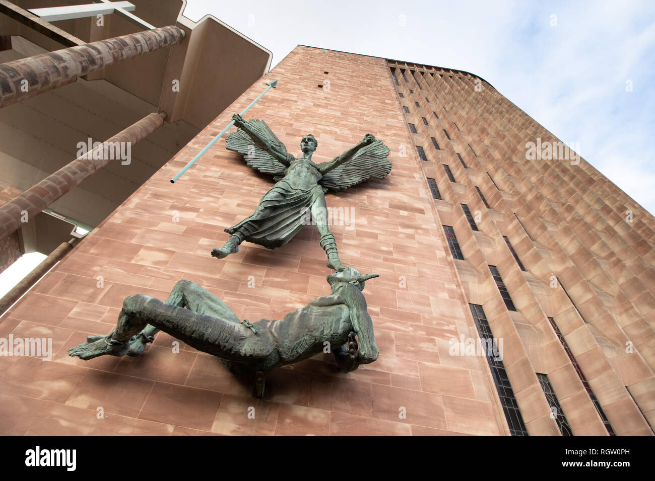 St Michael's victory over the Devil is portrayed in this statue by Sir Jacob Epstein, mounted on the side of the new Coventry Cathedral. - Stock Image