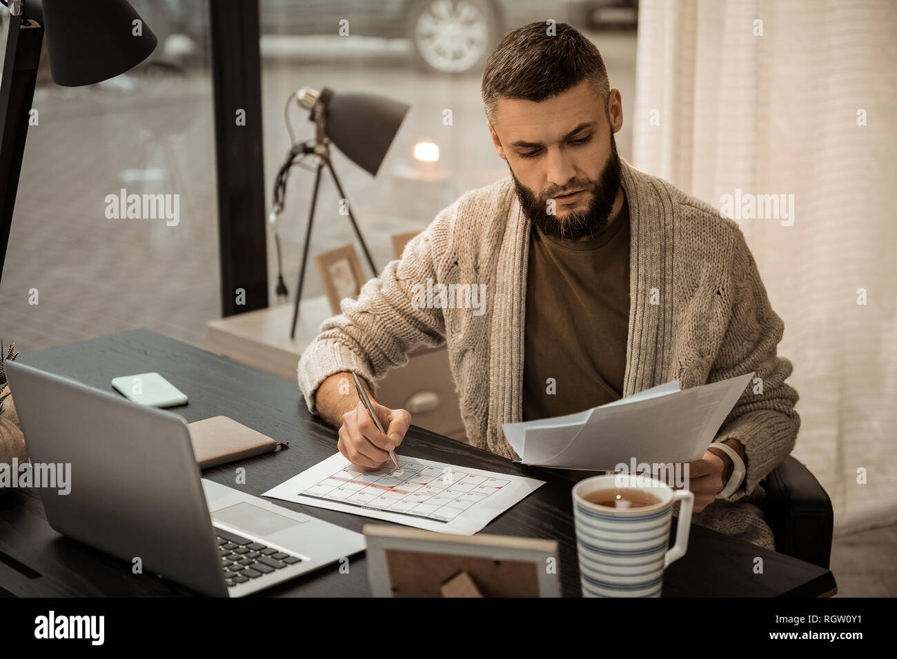 Confused self-employed bearded man flipping through papers - Stock Image