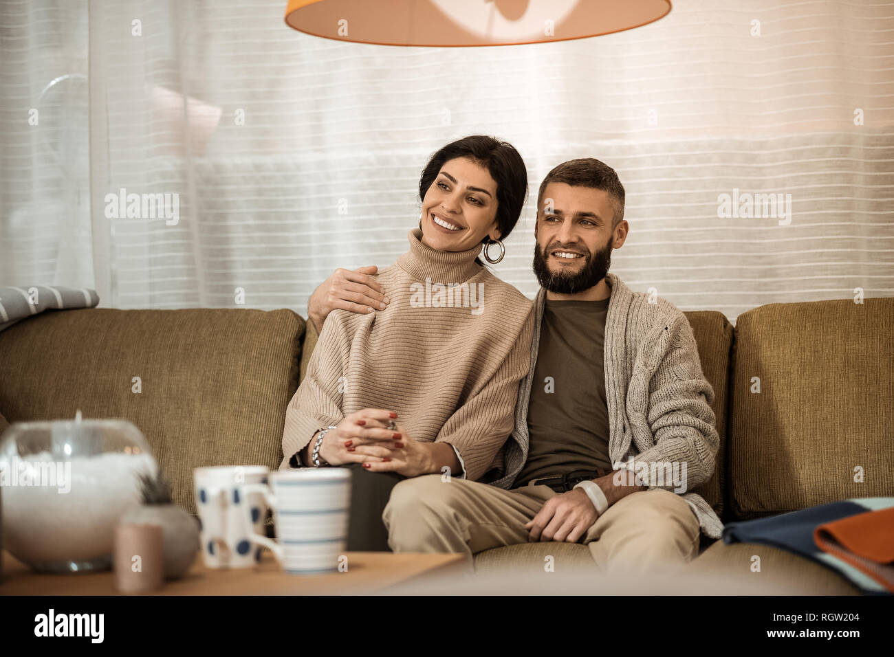 Dark-haired cute couple sitting extremely close to each other while watching TV - Stock Image