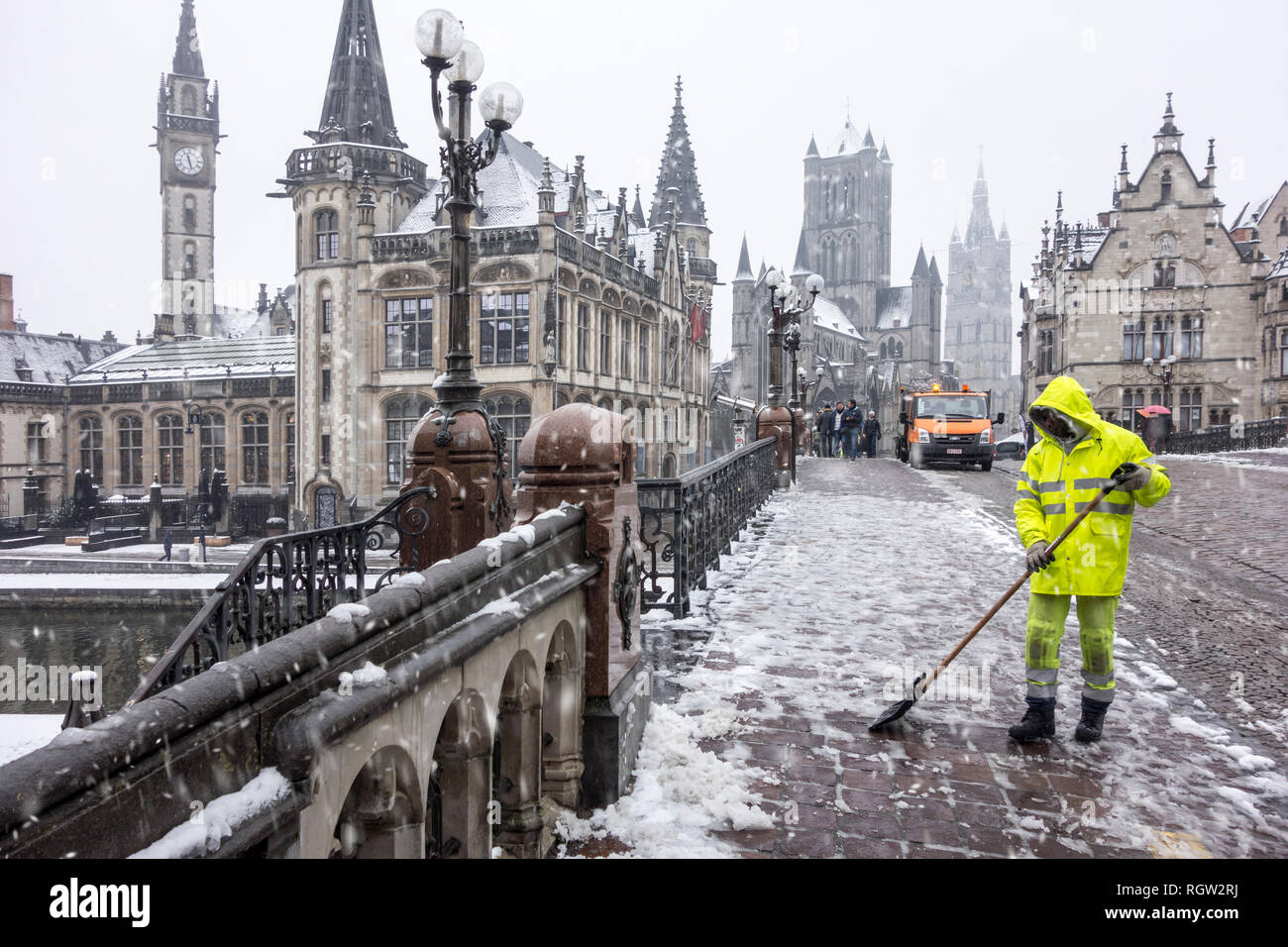 City worker cleaning pavement during sleet / snow shower in winter in the city Ghent, East Flanders, Belgium - Stock Image