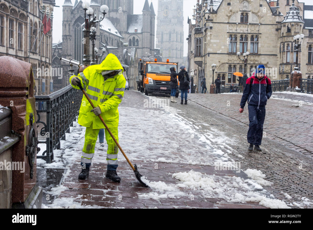 Pedestrians on slippery road and city worker cleaning pavement during sleet / snow shower in winter in the city Ghent, East Flanders, Belgium - Stock Image