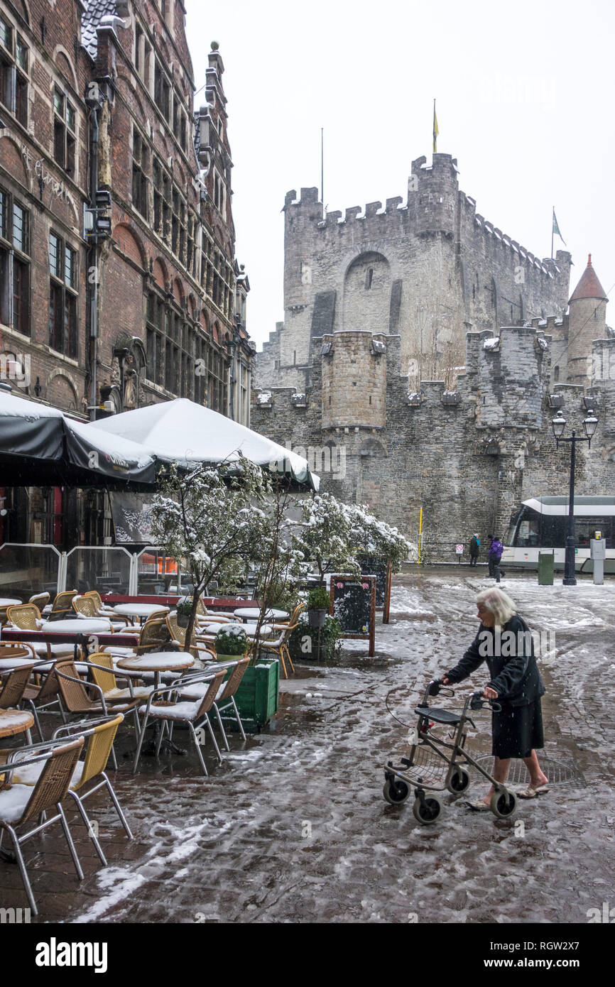 Elderly woman with rollator / wheeled walker walking on slippery pavement during sleet / snow shower in winter in the city Ghent, Flanders, Belgium - Stock Image