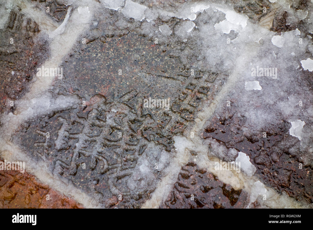 Footprints of pedestrian in wet snow / sleet on slippery pavement / dangerous sidewalk in winter - Stock Image