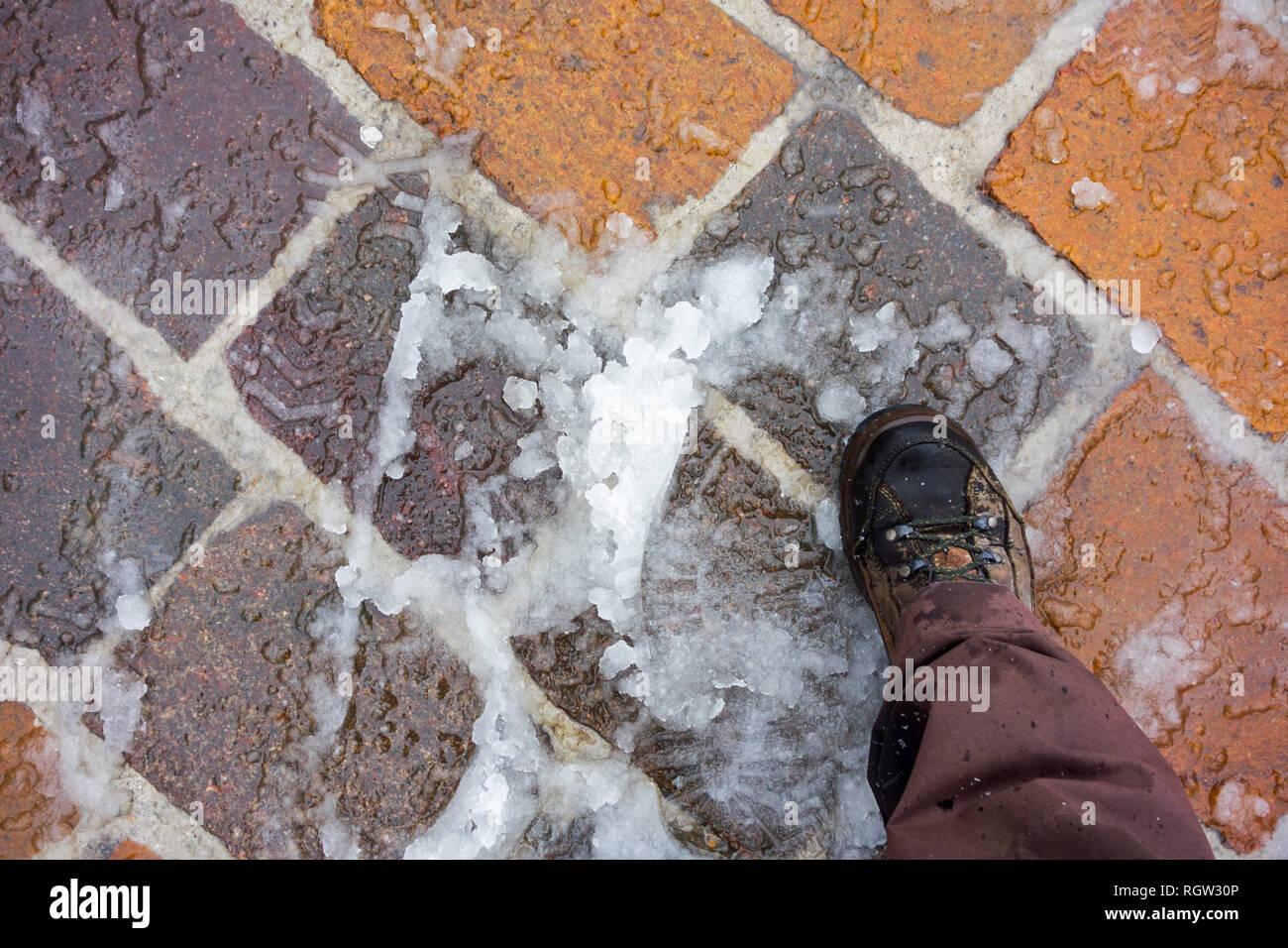 Shoe on wet snow / sleet on slippery pavement / sidewalk in winter - Stock Image