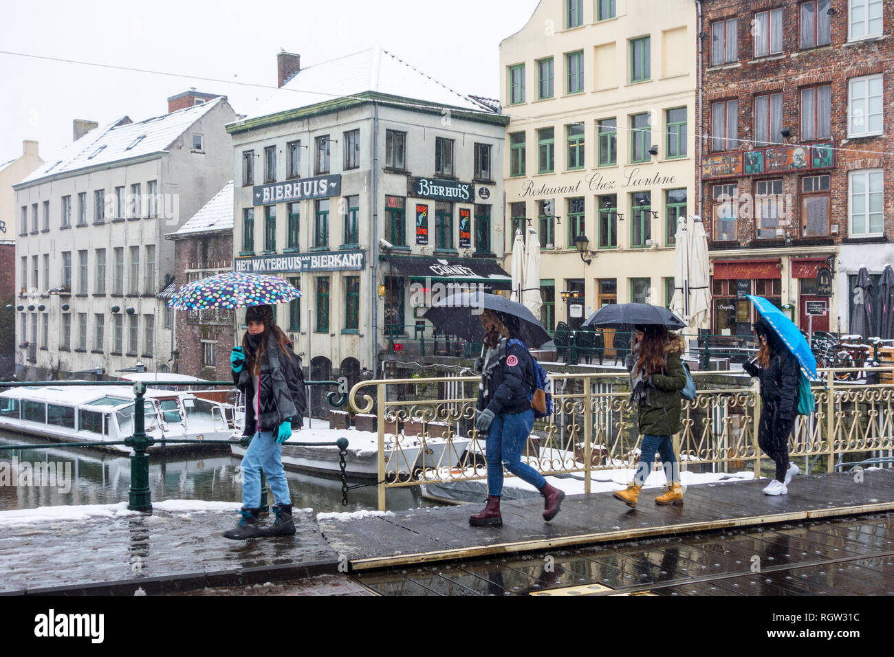 Tourists with umbrellas walking during snow shower / sleet in the city Ghent, East Flanders, Belgium - Stock Image