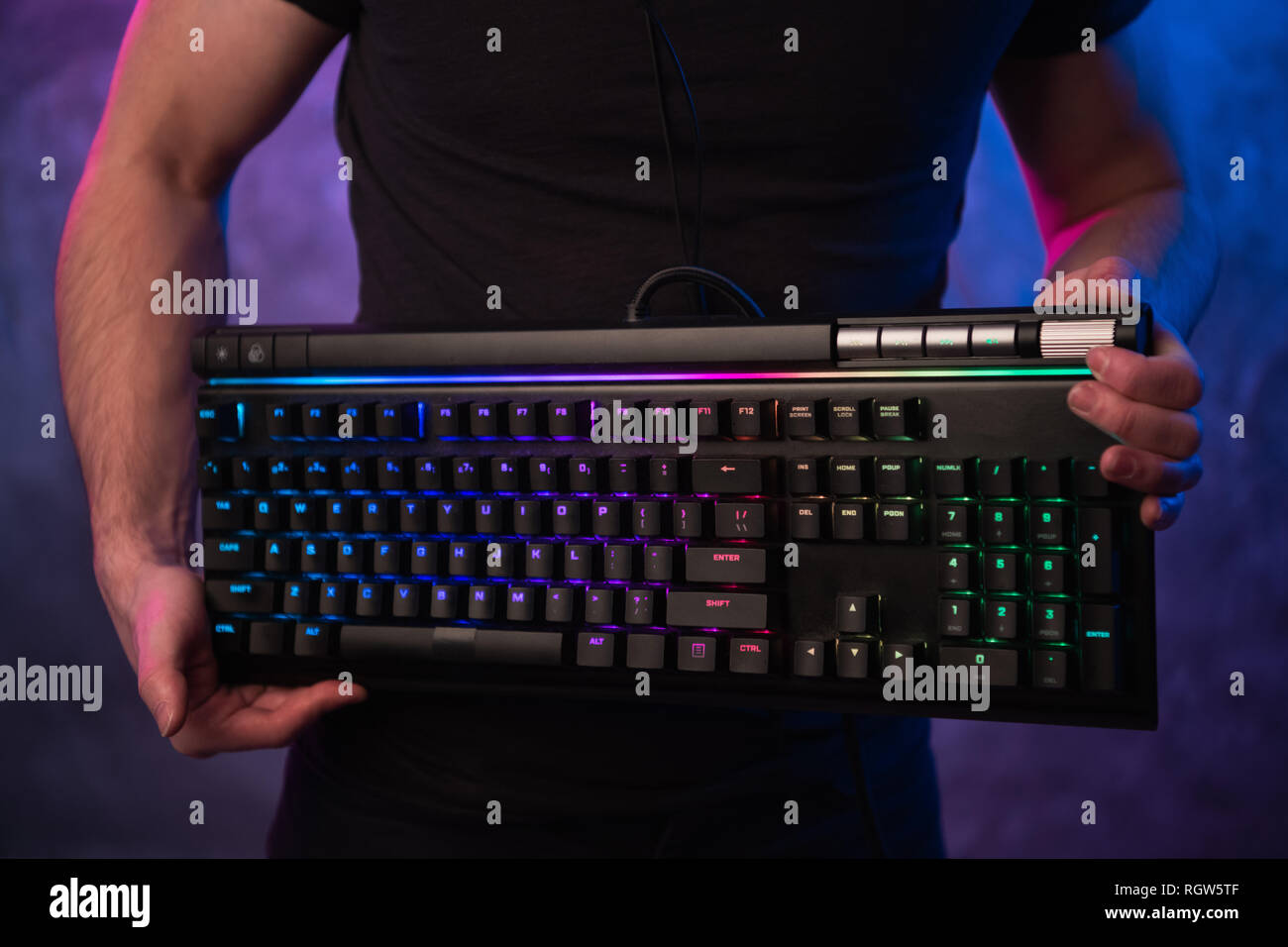 Close-up on gamer's hands holding a keyboard. Background is lit with neon lights - Stock Image