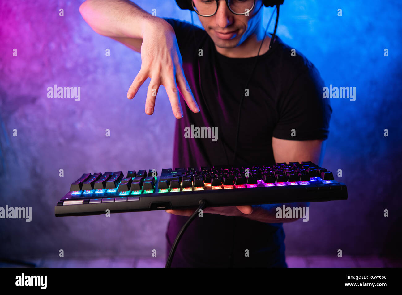 Close-up on gamer's hands going to press a key on a keyboard. Background is lit with neon lights - Stock Image