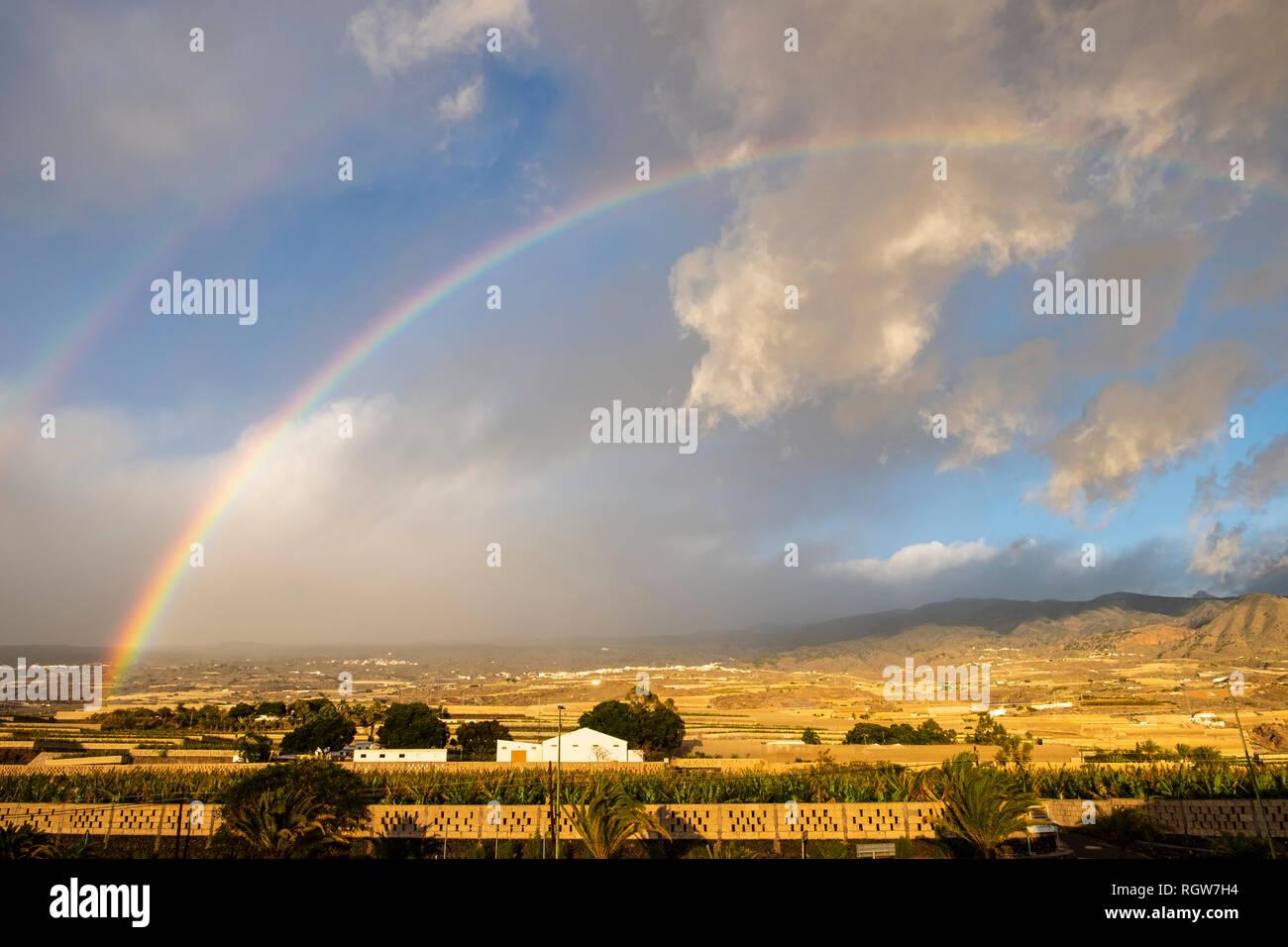 Colourful rainbow over banana plantations in Playa San Juan, Tenerife, Canary Islands, Spain - Stock Image