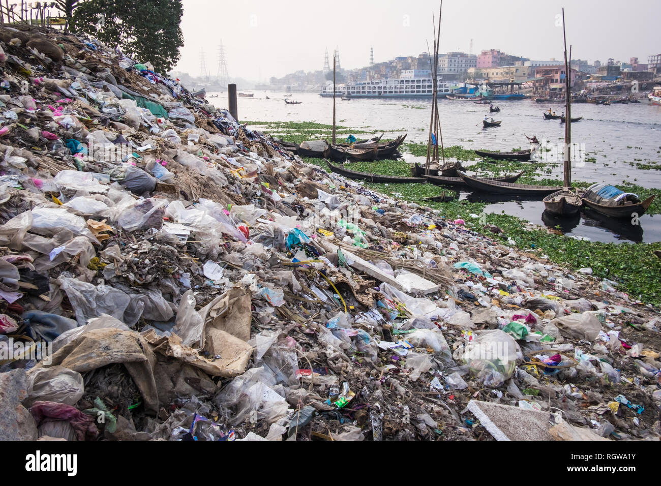 garbage and plastic pollution on the river bank in Dhaka, Bangladesh, riverside and boats in the background - Stock Image