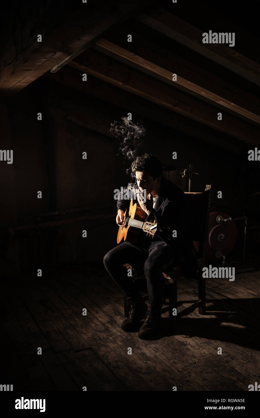 Guy playing on guitar and smoking cigarette on chair on garret in darkness - Stock Image