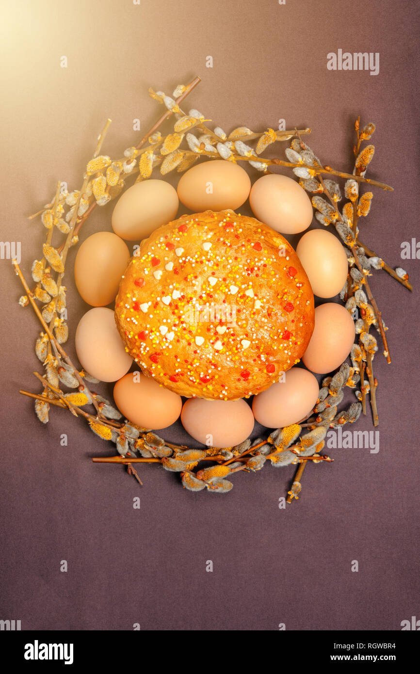 Easter bread in a circle of Easter eggs and a willow branch, a texture 2019 - Stock Image